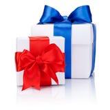 Dos cajas blancas atadas con el arco rojo y azul de la cinta de satén aislado Imagen de archivo