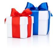 Dos cajas blancas atadas con el arco rojo y azul de la cinta de satén aislado Imágenes de archivo libres de regalías
