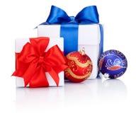 Dos cajas blancas atadas con el arco rojo y azul de la cinta de satén, bolas de la Navidad en el fondo blanco Imágenes de archivo libres de regalías