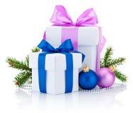 Dos cajas blancas ataron el arco de la cinta rosada y azul, la rama de árbol de pino y las bolas de la Navidad aislados en blanco Foto de archivo