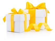 Dos cajas de regalo blancas ataron un arco amarillo de la cinta aislado Foto de archivo