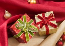 Dos cajas de regalo con los arcos, en las telas de satén onduladas rojas y de oro con las bolas de la Navidad Foto de archivo libre de regalías