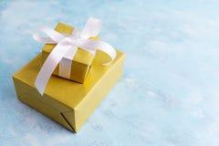 Dos cajas de regalo en oro empapelan el arco blanco del witn en fondo azul Concepto del día de fiesta Año Nuevo, la Navidad, cump Imagenes de archivo
