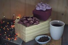 Dos cajas de regalo, granos de café en un cuenco, una taza de café en un tablennn Imagen de archivo libre de regalías