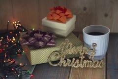 Dos cajas de regalo, taza de café y casan la Navidad en el tablenn Foto de archivo libre de regalías
