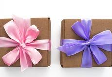Dos cajas de regalo de vacaciones atadas con la cinta de satén en el fondo blanco imágenes de archivo libres de regalías