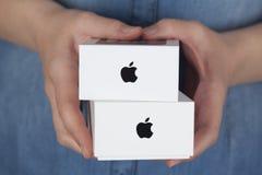 Dos cajas del iPhone de Apple en las manos de la mujer Imagen de archivo libre de regalías