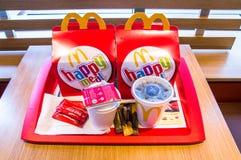 Dos cajas felices de la comida de Mcdonalds con el té de Lipton, Coca-Cola, la salsa de tomate de tomate y el azúcar Imagen de archivo