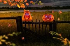Dos calabazas anaranjadas malvado de risa con brillar intensamente observan en la cerca de madera en la noche foto de archivo