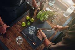 Dos camareros que experimentan con las nuevas recetas para el cóctel Imágenes de archivo libres de regalías