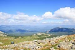 Dos caminantes con las mochilas que se colocan encima de la montaña Fotografía de archivo libre de regalías
