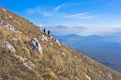 Dos caminantes en el senderismo a través de la montaña Rtanj en un día soleado Fotografía de archivo libre de regalías