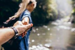 Dos caminantes en la naturaleza que cruza la corriente que celebra las manos Imagen de archivo