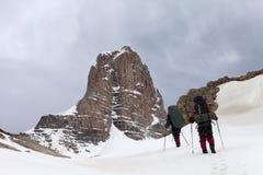 Dos caminantes en montañas nevosas antes de la tormenta Foto de archivo