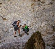 Dos caminantes en un acantilado de la montaña Fotos de archivo