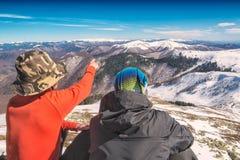 Dos caminantes en una colina gozan del valle con los picos de montaña Fotos de archivo
