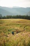 Dos caminantes que caminan abajo de un rastro junto en las montañas Fotos de archivo
