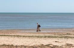 Dos caminantes que caminan a lo largo de la playa abandonada junto Foto de archivo libre de regalías