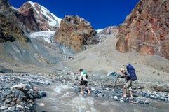 Dos caminantes que cruzan el río de la montaña Imagen de archivo libre de regalías