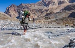 Dos caminantes que cruzan el río de la montaña Fotografía de archivo