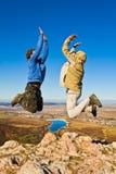 Dos caminantes que saltan alegre en cumbre de la montaña fotos de archivo