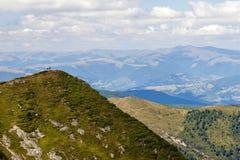 Dos caminantes que se colocan en un acantilado enorme de la montaña Caminar el turismo Po Fotos de archivo libres de regalías