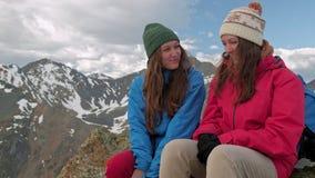 Dos caminantes que se relajan encima de la colina y que disfrutan de salida del sol sobre el valle almacen de metraje de vídeo
