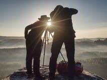 Dos caminantes que toman imágenes y charla encima de la montaña Dos fot?grafos libre illustration