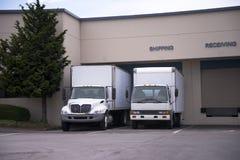 Dos camiones de la clase media semi con los remolques de la caja se colocan en muelle encendido fotografía de archivo