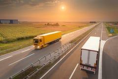 Dos camiones de reparto en la carretera vacía en la puesta del sol imágenes de archivo libres de regalías