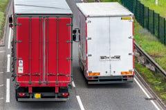 Dos camiones del camión de la caja en la autopista británica en el movimiento rápido fotos de archivo