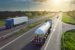 Dos camiones en la carretera en la puesta del sol en el movimiento Fotos de archivo libres de regalías