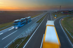 Dos camiones en la falta de definición de movimiento en la autopista sin peaje en la puesta del sol Fotos de archivo libres de regalías