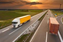 Dos camiones en la falta de definición de movimiento en la carretera en la puesta del sol Fotos de archivo libres de regalías