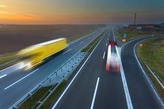 Dos camiones en la falta de definición de movimiento en la carretera en la puesta del sol Fotografía de archivo
