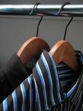 Dos camisas con estilo en perchas de madera imagen de archivo libre de regalías