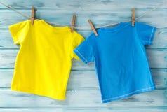 Dos camisetas brillantes del bebé que cuelgan en una cuerda para tender la ropa en un fondo de madera azul foto de archivo libre de regalías