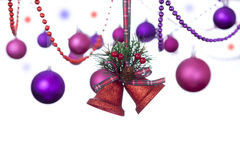Dos campanas rojas del brillo que cuelgan en una cinta del tartán con las chucherías de la Navidad Imágenes de archivo libres de regalías