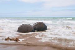 Dos cantos rodados esféricos de los cantos rodados de Moeraki en la alta marea Foto de archivo libre de regalías