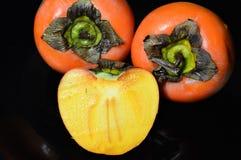 Dos caquis y unas mitad de la fruta en la placa negra Fotos de archivo