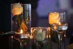Dos caramelos y rosas blancas, romance, objetos, cena por el candlel Fotografía de archivo libre de regalías