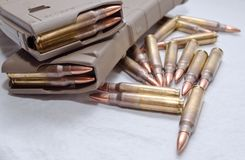 Dos cargados 223 revistas del rifle con las balas que ponen alrededor de ellas Imagen de archivo libre de regalías