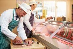 Dos carniceros que preparan la carne en tienda Fotos de archivo