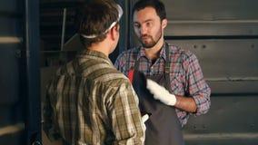 Dos carpinteros tienen un diálogo en taller almacen de metraje de vídeo