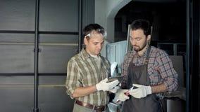 Dos carpinteros tienen una discusión usando la tableta digital imágenes de archivo libres de regalías