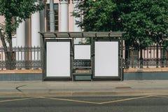 Dos carteleras blancas en blanco verticales en la parada de autobús en la calle de la ciudad En los edificios y los árboles del f imagen de archivo