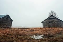 Dos casas viejas del granero en los campos lluviosos Fotos de archivo
