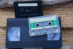Dos casetes audios y una cinta de video en la madera Fotos de archivo