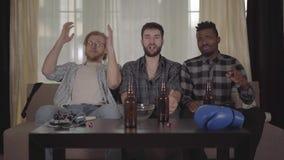Dos caucásicos felices y hombres afroamericanos uno que descansan junto en casa, boxeo de observación en la TV Botellas de cerv almacen de metraje de vídeo