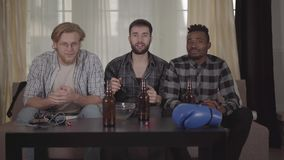 Dos caucásicos y hombres afroamericanos uno que descansan junto en casa, boxeo de observación en la TV Botellas de cerveza, mic almacen de metraje de vídeo